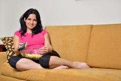 Etend popcorn op laag - TV-afstandsbediening royalty-vrije stock foto's