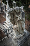 The eternal embrace. Funerary statue of a man clinging to a cross located in the old courtyard of the Catholic cemetery of Granada. Spain Granada Cemetery Stock Photos