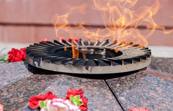 Eternal flame. And flowers in memory of the Victory in the Great Patriotic War Stock Image