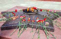 Eternal flame and flowers Stock Photo