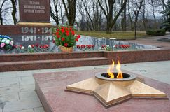 Eternal Flame, memory of the fallen. Burning flame of eternal fire on a background of a monument to victims Royalty Free Stock Images