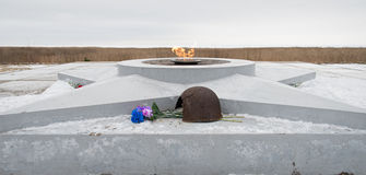 The eternal flame, in memory of the victims of 1941-1945, a bullet Pierced the helmet. Flowers Stock Image