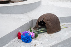 The eternal flame, in memory of the victims of 1941-1945, a bullet Pierced the helmet. Flowers Royalty Free Stock Photography