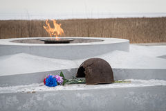 The eternal flame, in memory of the victims of 1941-1945, a bullet Pierced the helmet. Flowers Stock Photography