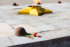 The eternal flame, in memory of the victims of 1941-1945, a bullet Pierced the helmet. Flowers Royalty Free Stock Images