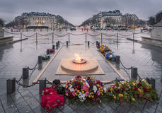 Eternal Flame in Paris on rainy day. Paris, France - February 13, 2016: The Eternal flame and the monument for the unknown soldier, under the Arc de Triomphe Stock Photos