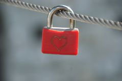 Eternal love. Padlock with heart symbolizing eternal love on a steel wire attached on a bridge stock image