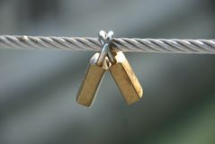 Eternal love. Two padlocks symbolizing eternal love on a steel wire attached on a bridge royalty free stock image