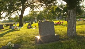Eternal Rest. Late afternoon in a cemetery in South Dakota. A star-shaped flare accents one corner of a large, pink granite tombstone in the foreground stock photos