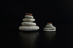 Eternal rocks and tranquility in the soul. A set of smooth stones on a black background, stacked in the order Stock Photo