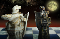 The eternal struggle between two opposites. Two chess pieces attack each other on the background of sky Stock Image