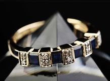 Eternity ring. Gold ring with blue sapphires and diamonds Stock Image