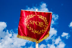 Eternity. Roman SPQR vexillum. Flag-like standard with the famous abbreviation Senatus Populusque Romanus (The Senate and People of Rome) against blue sky and stock images