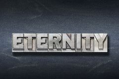 Eternity word den. Eternity word made from metallic letterpress on dark jeans background royalty free stock photos