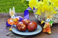 Eterscène met paaseieren, gele narcisbloemen en stuk speelgoed konijntjes Stock Foto's