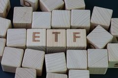 ETF,交换被换的资金概念,与建立词ETF的字母表的立方体木块在黑暗的黑板的中心 免版税库存图片
