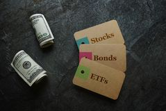 ETFs Stocks and Bonds. ETF Exchange Traded Funds, Stocks and Bonds paper tags with money Royalty Free Stock Image