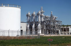 Ethanol Plant. In the midwest with green grass in foreground and clear blue sky above Stock Photo