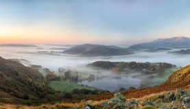 Ethereal autumn sunrise over the Langdale valley, Lake District. An autumn sunrise across a clear sky in the Langdale Valley in the Lake District UK, with Royalty Free Stock Photo