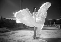 Ethereal, divine bride with flying, shiny dress standing in temp Royalty Free Stock Photos