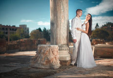 Ethereal, divine bride with shiny dress and groom standing near. Temple ruins. Ancient mosaic and floor Royalty Free Stock Photo