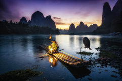 Ethereal Night. Old cormorant fisherman by the li river in xingping. Fisherman with the lantern on near the shoreline Stock Images