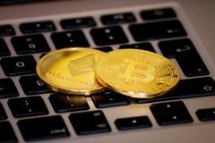 Ethereum и cryptocurrency bitcoin чеканят над клавиатурой стоковые фотографии rf