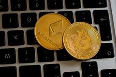 Ethereum и cryptocurrency bitcoin чеканят над клавиатурой стоковые изображения