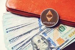 Ethereum auf Stapel von US-Dollar Rechnungen, Hälfte innerhalb einer orange Geldbörse Lizenzfreies Stockbild