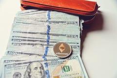 Ethereum auf Stapel von US-Dollar Rechnungen, Hälfte innerhalb einer orange Geldbörse Stockbilder