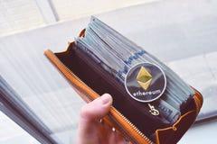 Ethereum auf Stapel von US-Dollar Rechnungen, Hälfte innerhalb einer orange Geldbörse Lizenzfreies Stockfoto