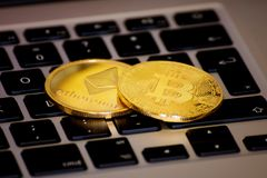 Ethereum and bitcoin cryptocurrency coin over a keyboard royalty free stock photos