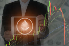 Ethereum and Blockchain concept. Rise and fall of Ethereum price. Businessman holding tablet showing Ethereum symbol with price chart and money in background Royalty Free Stock Photo