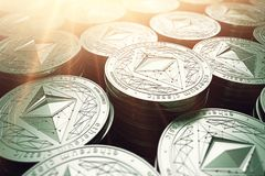 Ethereum classic ETC coins in blurry closeup with sunburst from above Stock Photography