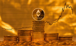 Ethereum coin against background of price graph. Single ethereum coin on stack of gold coins with graph of price change against US dollar in background Royalty Free Stock Photo