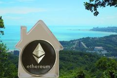 Ethereum coin in a metal house. On a sea cost background. Rent or buy a house for ETH Royalty Free Stock Photography