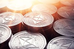 Ethereum coins ETH in blurry closeup with sunburst from above. Royalty Free Stock Photography