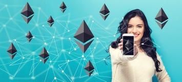 Ethereum com a jovem mulher que guarda para fora um smartphone fotografia de stock