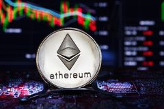 Ethereum. Crypto currency. Ethereum real coin on the computer board and a chart on background. Blockchain technology stock images