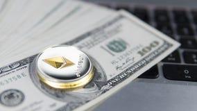 Ethereum cryptocurrency överst av 100 dollarbiils på en bärbar dator Vinst från att bryta crypto valutor Gruvarbetare med dollar Royaltyfri Bild