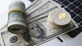 Ethereum cryptocurrency överst av 100 dollarbiils på en bärbar dator Vinst från att bryta crypto valutor Gruvarbetare med dollar Arkivbild