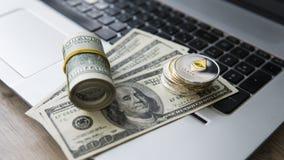 Ethereum cryptocurrency överst av 100 dollarbiils på en bärbar dator Vinst från att bryta crypto valutor Gruvarbetare med dollar Arkivfoton