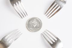 Ethereum cryptocurreny silver coin placed between forks on white background, hard fork stock images