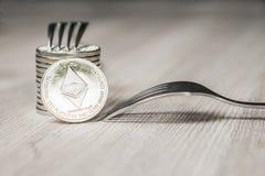 Ethereum, das neue harte Gabel-Änderung, körperliche silberne Crytocurrency-Münze mit Gabel, Blockchain-Konzept erhält stockfotografie