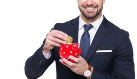 Ethereum de baisse d'homme d'affaires dans le smil toothy conceptuel de tirelire Image stock