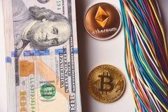 Ethereum e bitcoin, cavi e noi 100 banconote in dollari Fotografia Stock Libera da Diritti