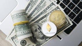 Ethereum en Bitcoin-cryptocurrency bovenop dollar 100 biils op laptop Winst van mijnbouwcrypto munten mijnwerker Stock Afbeeldingen