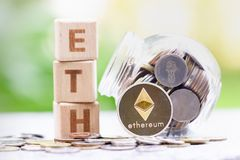 Ethereum ETH  Coins and Wood block word ETH on blurred greenery background. stock images