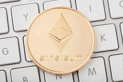 Ethereum golden cryptocurrency coin on keyboard Stock Photography