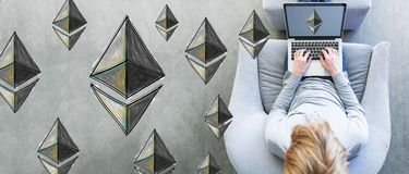 Ethereum with man using a laptop. In a modern gray chair Royalty Free Stock Photography